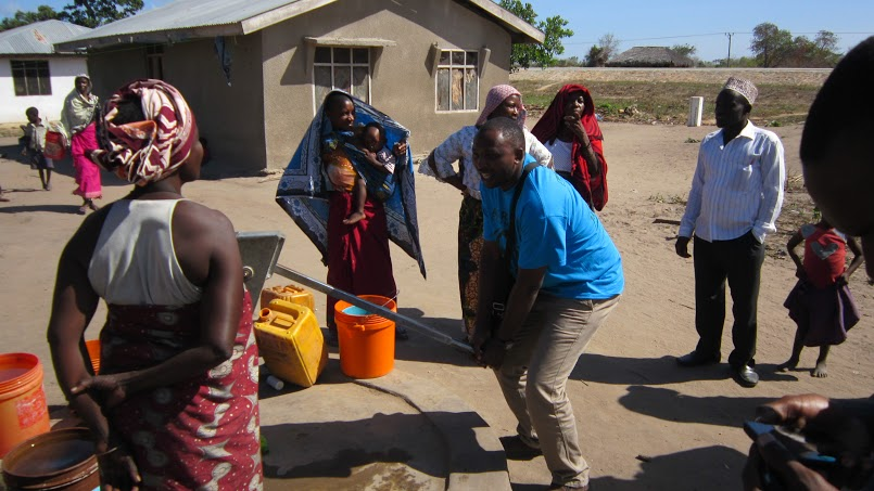 Finance Director Victor Mwenda helping pump from the well