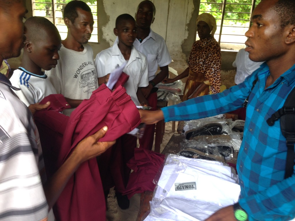ACAI worker Shadad passes out materials to students for an Education in Africa